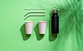 Plastic-free objects flat lay. Reusable drinking containers isolated on green background