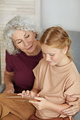 Senior Woman Using Tablet with Girl