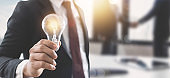 Innovation and idea of professional leader holding lighting bulb, business people making handshake after successful working, brainstorming teamwork and thinking management concept