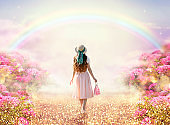 Lady woman in romantic pink dress and retro hat walking along rose garden path leading to fabulous rainbow unicorn house, flecks of sunlight on road. Tranquil fantasy scene, fairytale hills.