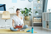 Woman Using Digital Tablet during Home Workout