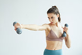 Motivated Young Woman Working Out with Dumbbells