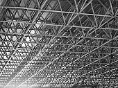 Metal truss frame roof of factory in black and white color with flare.