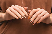 Female hands with blue nail design. Blue nail polish manicure. Woman hands on brown fabric background.