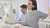 Tired Creative Woman having Back Pain in Modern Office