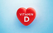 Vitamin D Written Red Heart Shape on Blue Background