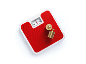Red Bathroom Scale and Bronze Weights on White Background