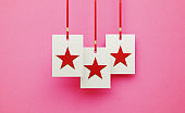 Red Stars over White Square Shapes Hanging from Red Ribbons over Pink Background
