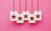 Red Stars on White Square Shapes Hanging from Red Ribbons over Pink Background