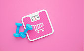 Shopping Cart Symbol Drawn Pink Bathroom Scale and Blue Dumbbells on Pink Background