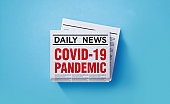 COVID-19 Pandemic Concept - Newspaper with COVID-19 Pandemic Headline Sitting on Newspaper Pile over Blue Background