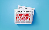 Newspaper with Reopening Economy  Headline Sitting on Newspaper Pile over Blue Background
