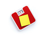 Red Bathroom Scale and Yellow Post It Note on White Background