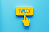 Hand Shaped Computer Cursor Clicking over A Yellow Push Button: Tweet Written on Push Button
