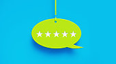 Five Stars Imprinted on Green Speech Bubble Hanging over Blue Background