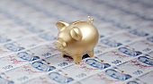Gold Colored Piggy Bank Sitting over One Hundred Turkish Liras Banknotes - Stock Market and Finance Concept
