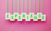 Experience Writes on White Price Tags Hanging from Green Ribbons over Pink Background