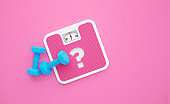 Question Mark Drawn Pink Bathroom Scale and Blue Dumbbells on Pink Background
