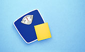 Blue Bathroom Scale and Yellow Post It Note on Blue Background