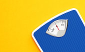 Blue Bathroom Scale on Yellow Background