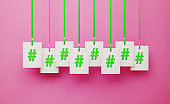 Hashtag Symbols on White Price Tags Hanging from Green Ribbons over Pink Background