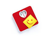 Red Heart Shaped Bathroom Scale and Yellow Post It Note on White Background