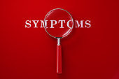 Magnifier And Symptoms Text on Red Background