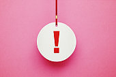 Exclamation Point on White Circle Label Hanging from Red Ribbon over Pink Background