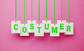 Costumer Writes on White Price Tags Hanging from Green Ribbons over Pink Background