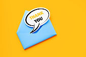 Blue Envelope and Speech Bubble Shaped Thank you Note Sitting on Yellow Background
