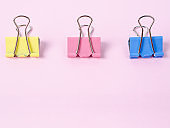 Colorful binder clips on pink paper background
