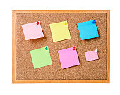 Blank sticky notes pinned on cork memo board