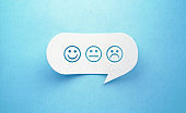 Smiley and Sad Faces Written White Chat Bubble On Blue Background