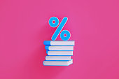 Blue Percentage Sign Sitting above A Blue Book Stack over Pink Background