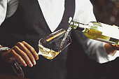 Close up photo, sommelier pouring white wine into wineglasses.