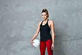 Volleyball girl hold and kick ball in black costume on grey concrete wall background