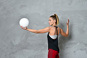 Young woman volleyball player on gray background