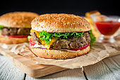 Classic tasty hamburger with beef, sauce and french fries on dark back