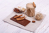 brown detox coctail with cinnamon sticks and chocolate lie on th