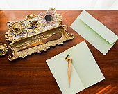 Brass inkwell on wood desk with mint green stationary envelope and pen