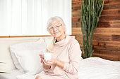 Happy smiling senior woman drinking coffee .