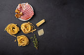 Ingredients of pasta fettuccine with mushrooms, bacon and parmesan cheese. Raw food on a dark graphite background top view