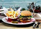 Burger with fries, pickles and plenty of meat with salad