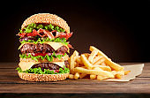 burger with french fries on wooden background.