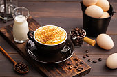 A cup of egg coffee on wooden table