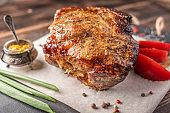 Homemade baked pork meat with vegetables and spices on a serving board on a wooden background. Close up. Selective focus