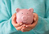 Female hand holding piggy bank