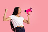 Portrait of a young woman being loud and heard by shouting through megaphone with fist up and mouth open