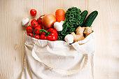 Fresh vegetables in cloth bag on light wooden background