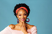 Portrait of a happy young woman in pink smiling and thinking with finger on mouth